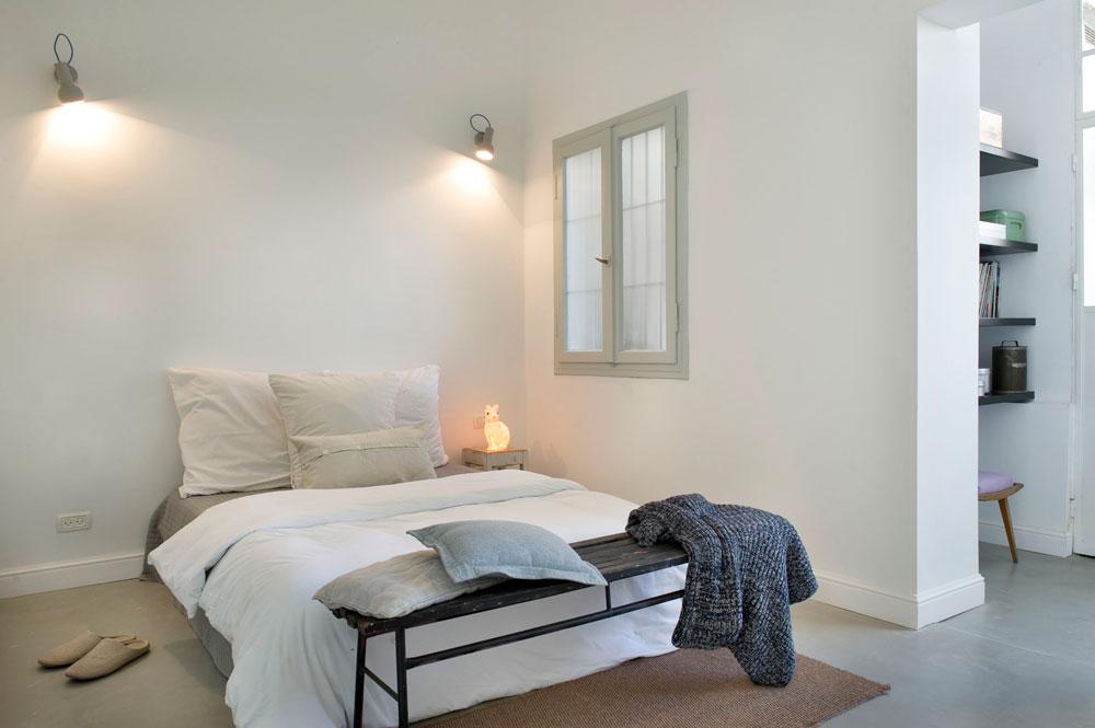 המיטה נצבעה באפור-ירקרק, כצבע החלון וארון הקיר שמולו. הספסל נמצא ברחוב ושופץ. מימין נראית הספרייה שבקצה פינת העבודה, במרפסת האחורית לשעבר (צילום: גלית דויטש)