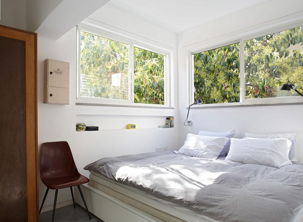 """חדר ההורים ממוקם בקצה הדירה, מוקף בשלושה חלונות שדרכם נראה עץ אבוקדו.  המיטה תוכננה כבמה """"מקיר לקיר"""", שבה גם מגירות לאחסון (צילום: עדי גלעד)"""