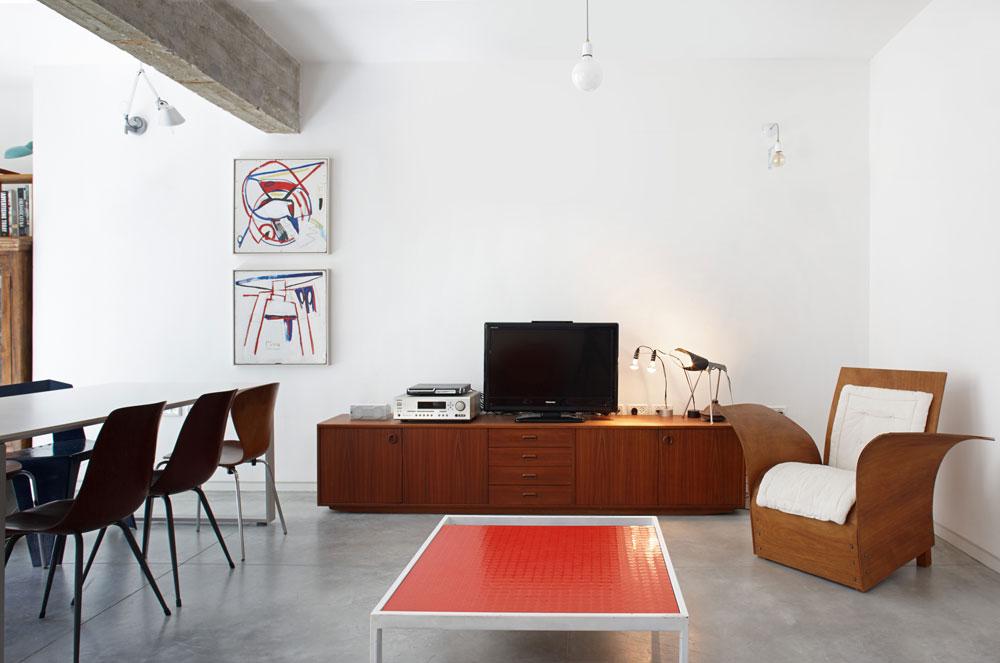 """בסלון יש רהיטים מחומרים שונים - עור, מתכת ופלסטיק - שעיצבו בני הזוג במשך השנים. """"חלק מהכסאות הם מלפני 20 שנה"""", אומר פורת (צילום: עדי גלעד)"""