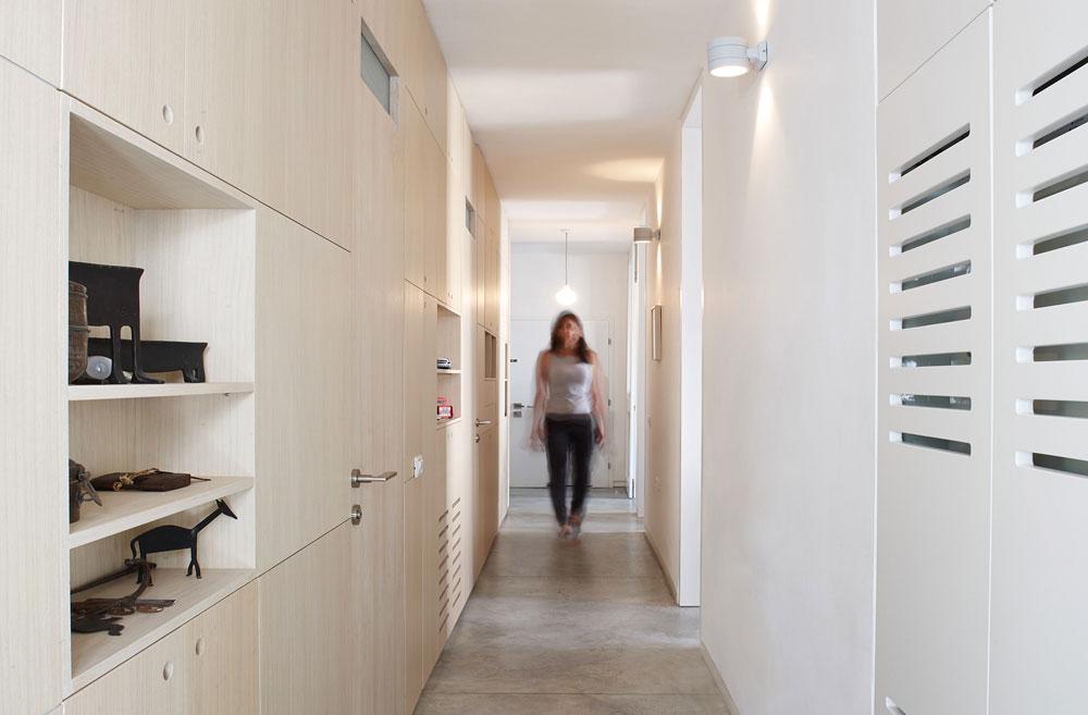 המסדרון בן 12 מטרים, ולו קיר אחד לבן, וקיר שני שכולו ארון מעץ אגוז (כולל דלתות הכניסה לחדרים) (צילום: עדי גלעד)