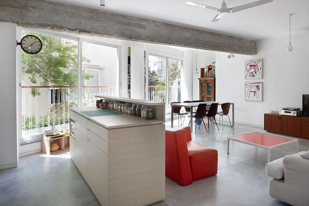 """המטבח מופרד מהסלון באמצעות """"אי"""" שבנוי מעץ אגוז לבן. אריחי הרצפה המקוריים הוסרו ובמקום יצקו בטון מוחלק (צילום: עדי גלעד)"""