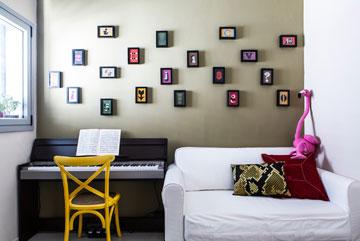 חדר אורחים בממ''ד, עם קיר שעוטר בגלויות שהוזמנו ברשת ומוסגרו (צילום: איתי בנית)