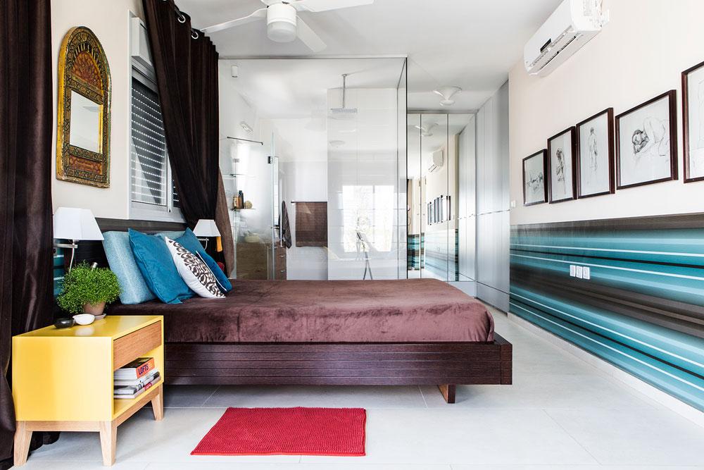 שני חדרים קטנים בקצה הדירה חוברו לחדר שינה מרווח, עם חדר רחצה שמופרד מהמיטה בקירות זכוכית. המרחב ''נעטף'' בטפט פסים ובווילונות קטיפה כבדים  (צילום: איתי בנית)