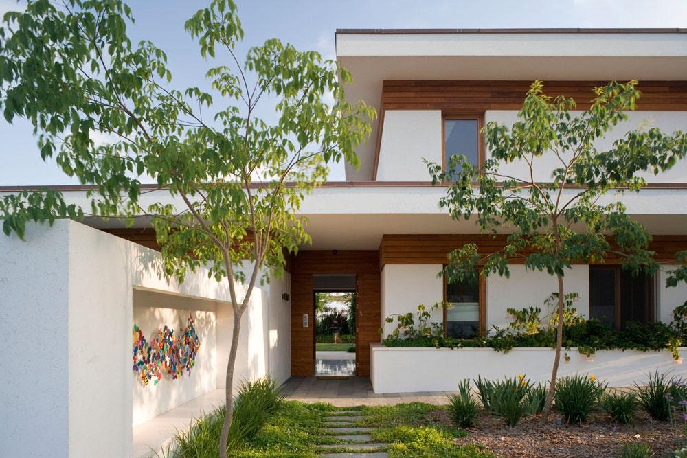 שביל הכניסה מלווה את הבית - מימינו אדנית בנויה, משמאלו גינה ומולו, בניצב לדלת הכניסה, קיר עם נישה גדולה, שבה נתלתה עבודת אמנות (צילום: מיקאלה בורסטאו)