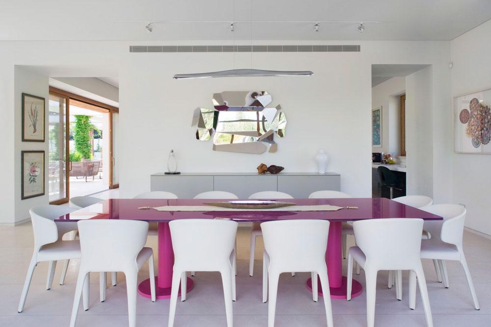 שולחן נועז בוורוד, כסאות לבנים ושידה אפורה שמעליה נתלתה מראה בחיתוך לא שגרתי (צילום: מיקאלה בורסטאו)