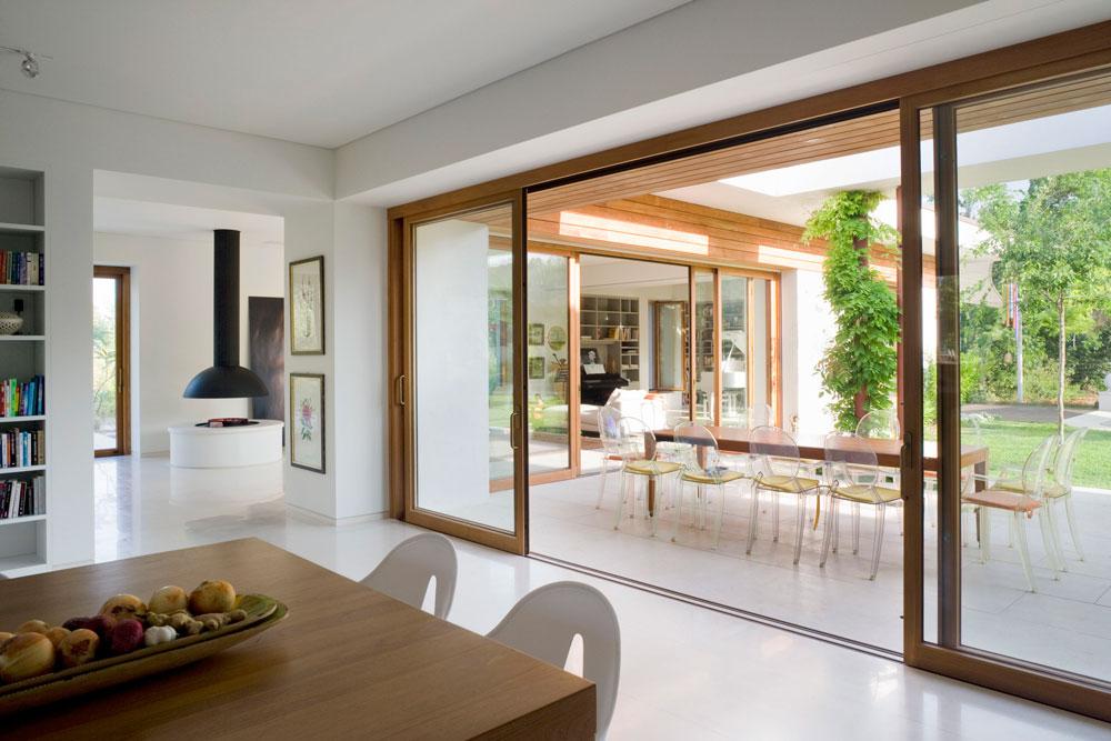 המטבח ניצב לחלל ארוך ופתוח, שבו פינת אוכל, סלון וספרייה שמקיפה פסנתר כנף לבן (צילום: מיקאלה בורסטאו)