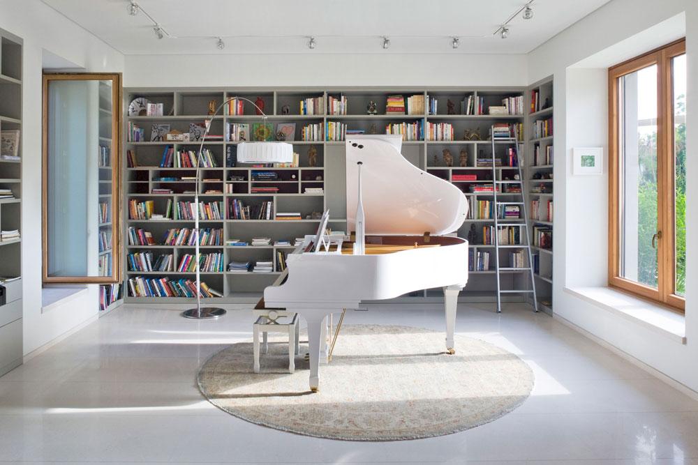 בקצה החלל הפתוח פסנתר כנף לבן, מוקף ספריות מעץ צבוע אפור (צילום: מיקאלה בורסטאו)