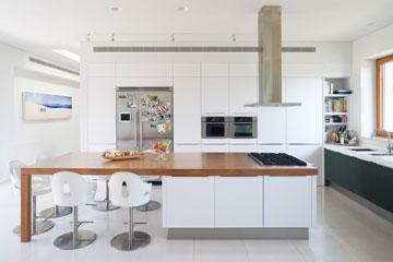 למטבח חזית אחת של ארונות לבנים וגבוהים וחזית שנייה של ארונות נמוכים, עם דלתות מזכוכית ירוקה (צילום: מיקאלה בורסטאו)