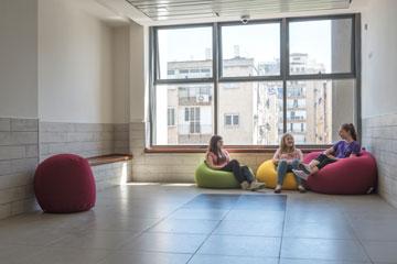 בקצה כל מסדרון, חלון שפונה לשכונה ופינת ישיבה עם פופים, אך בינתיים אסור לתלמידים לשבת עליהם (צילום: אלי סינגלובסקי )