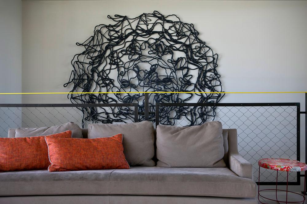 במעלה המדרגות, על הקיר מאחורי הספה, יצירה מפלסטיק ממוחזר, של האמן ירון אליאסי (צילום: שירן כרמל)