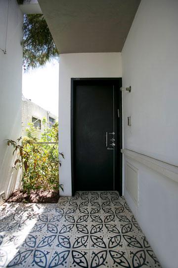 לפני דלת הכניסה מבואה מקורה, תחומה בקיר שעליו תטפס צמחייה (צילום: שירן כרמל)