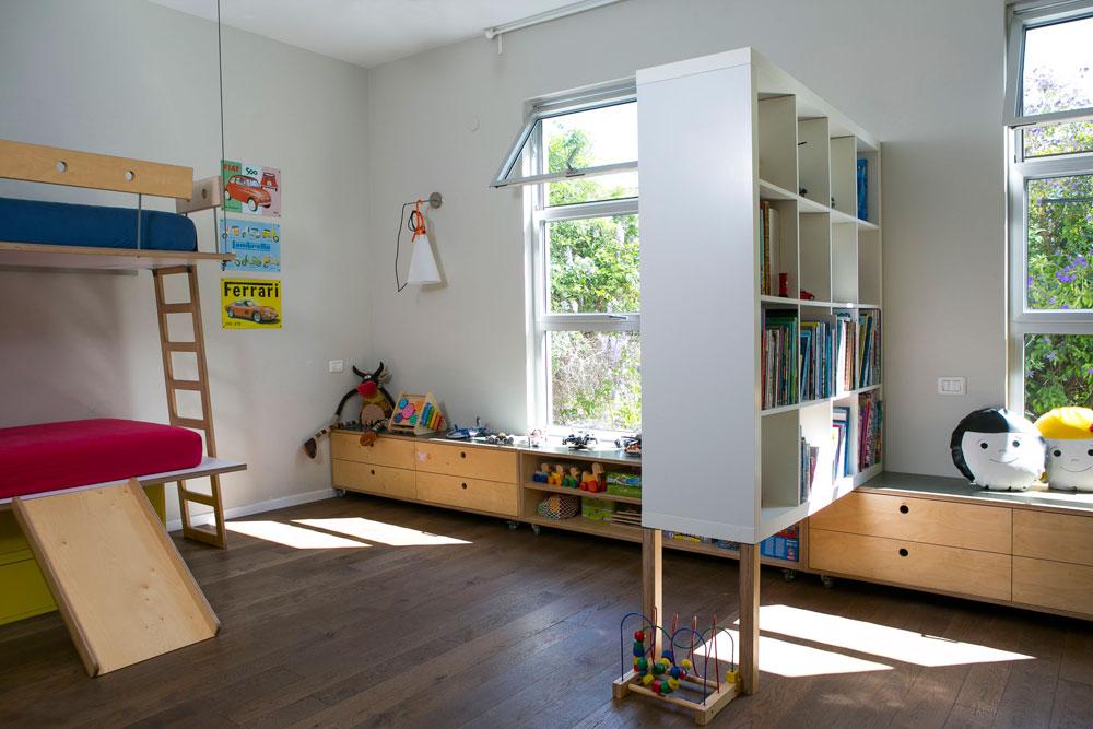 שלושת הילדים חולקים חדר גדול. כוורת איקאה פשוטה הועמדה על רגליים ומסמנת את המקום שבו יהיה אפשר בעתיד לבנות קיר ולחלק את החדר. שני חלונות נאים תוכננו לשם כך מראש (צילום: שירן כרמל)