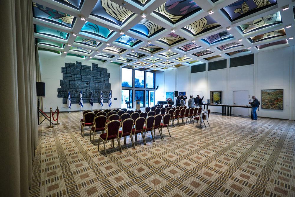 """אולם הטקסים. קיר הבזלת המשמש רקע לתמונות רבות הוא עבודה של משה קסטל בשם """"כותל תהילה לירושלים"""". את הרצפה עיצב היינץ פנחל, ואת התקרה מקשטים ציורים של נפתלי בזם (צילום: איתי סיקולסקי )"""