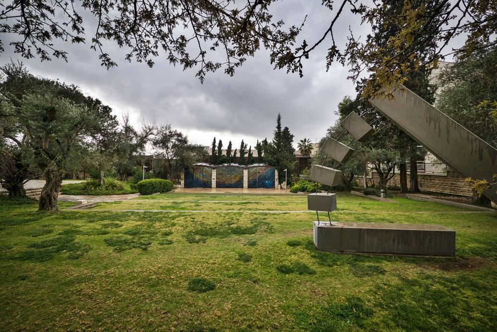 פסל של מנשה קדישמן בגן המקיף את הבניין. ברקע: קיר הזכוכית של בית הכנסת שעיצבה מירה מיילור (צילום: איתי סיקולסקי )