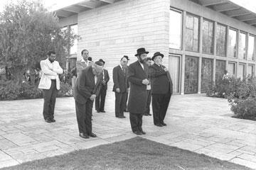 """השר אברהם שפירא מוביל תפילת מנחה בכניסה לבניין, 1981 (צילום: הרמן חנניה, לע""""מ)"""