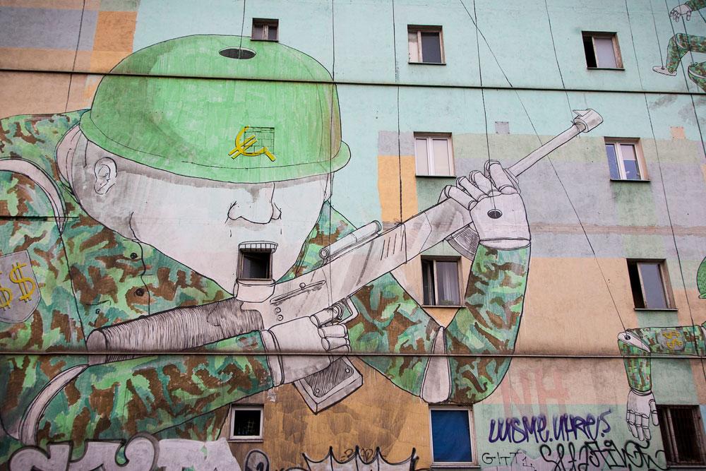אחד הדברים שקשה לפספס בשיטוטים בין רובעי העיר הם ציורי קיר עצומים, מלאים באמירות פוליטיות, בסוריאליזם ובהומור. בתמונה העבודה ''חיילי מריונטה'' של האמן האיטלקי blu, שמותח ביקורת על תרבות הצריכה ששולטת במזרח ומרכז אירופה (לחיילים יש סימן של יורו על הקסדה) כמו במערב (ודולר על הכותפות)  (צילום: אסי חיים)