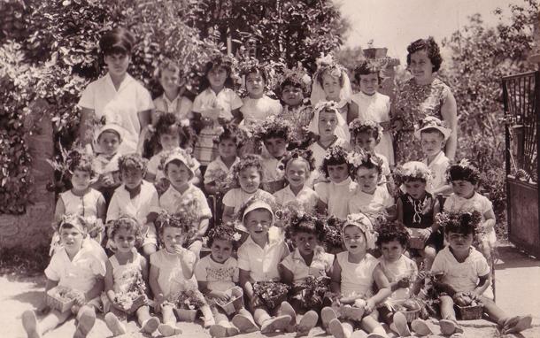 זר על הראש וטנא מבריסטול. רות ראונר (מימין) עם ילדי הגן שלה לקראת שבועות