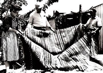 רחמים חג'ג' (מימין) ורות דיין בוחנים שטיח שנארג עבור מפעל ''משכית'' (צילום: מרכז תיעוד תל מונד)