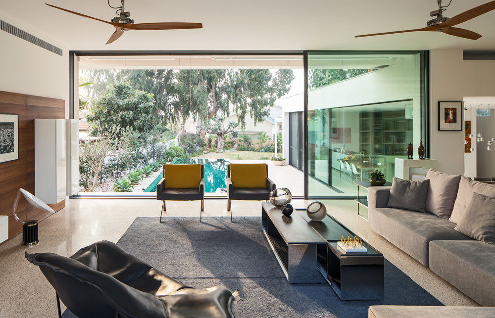 הנוף מודגש: זכוכית מהווה כמחצית מחזיתות הבית, שפונה לעצי אקליפטוס המשתקפים בבריכה. מבט מהסלון, שמוקם על מפלס מוגבה בקומת הכניסה (צילום: עמית גרון)