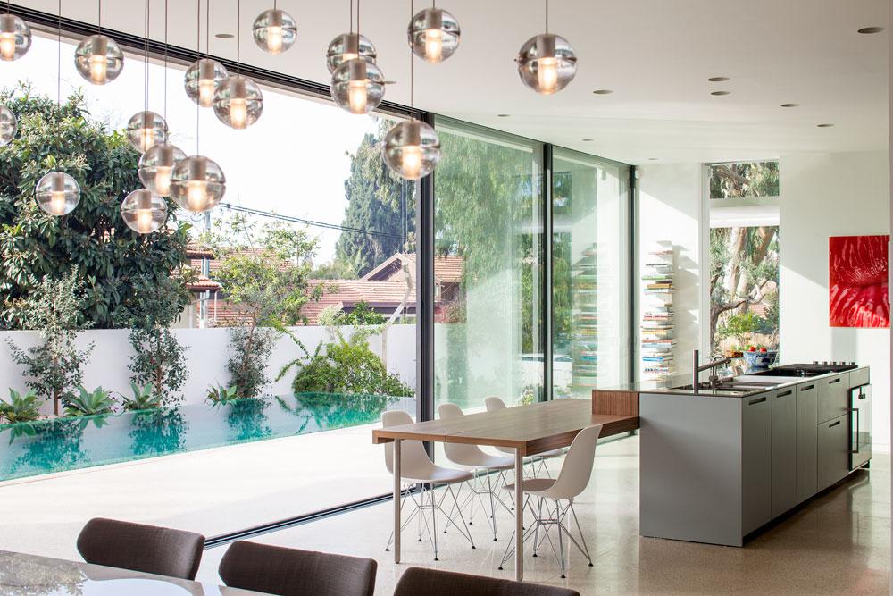 מעל שולחן האוכל מנורה של המותג ''בוצ'י'', והמטבח נסתר כולו, למעט האי במרכז. הארונות הם חזית אחידה ומבריקה בגוון ירוק-אפור, שמגיב לעוצמת האור (תמונה בהמשך הכתבה) (צילום: עמית גרון)