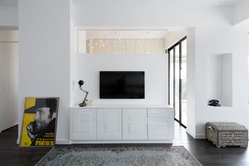 מבט מהספה אל חצי הקיר שמפריד בין הסלון למטבח. משמאל נראה המסדרון שמוביל אל דלת הכניסה (צילום: גדעון לוין, ''181 מעלות'')