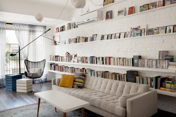 מדפים לכל אורך הקיר החשוף. בתמונות הסלון נדמה צר, אך זה בגלל אורכו. המרחק בין קיר לקיר ברוחב החדר הוא 385 ס''מ (צילום: גדעון לוין, ''181 מעלות'')
