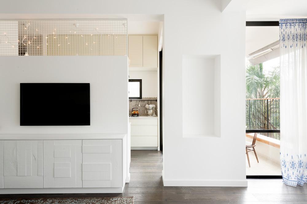 מבט מהסלון אל המטבח והמרפסת. שידת הטלוויזיה תוכננה עם דלתות משאריות עץ שנצבעו בלבן. במעלה הקיר רשת שמסמלת הפרדה אך לא חוסמת זרימה של אור ואוויר (צילום: גדעון לוין, ''181 מעלות'')