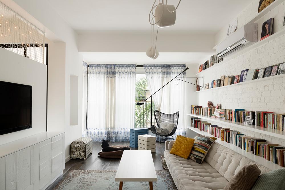 כל החדרים בדירה התל אביבית הישנה נשארו במקומם, אך מעט קירות נשברו כדי להוסיף מרחב ותנועה. הסלון הרוויח פינת קריאה על חשבון המרפסת הצמודה (צילום: גדעון לוין, ''181 מעלות'')