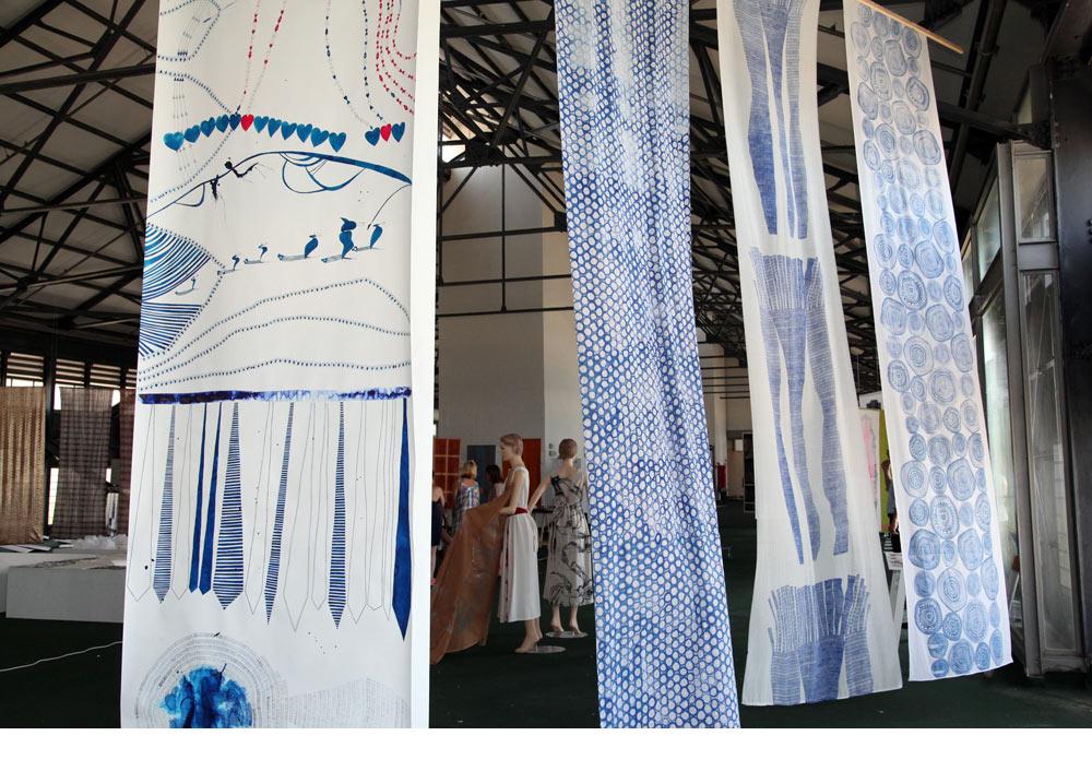 ''כחול לבן'' - הפרויקט של דקלה בן ארי, בחלל התצוגה בנמל יפו. שלוש יריעות בד לבנות שעליהן הדפסים עדינים וכובשים בכחול. משמאל יריעת נייר שעליה רשמה בעט איורים אסוציאטיביים. ''יש לה יכולת רישום ויצירה של עולמות'', אומר ראש המחלקה אורי צייג. ''שפה משלה, מיזוג בין אמנות לעיצוב. זה בעיני הפרקטיס הכי רלוונטי בעיצוב''. בן ארי מקווה לעצב תפאורות לתיאטרון (צילום: תמי דהן)