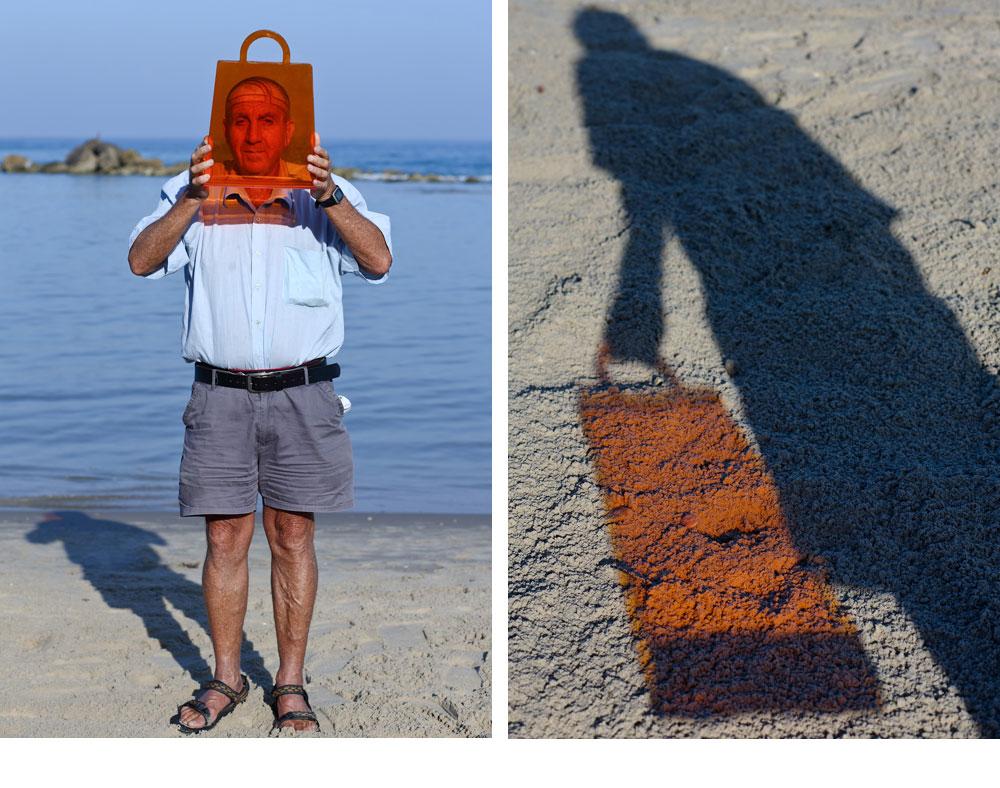 עוזי עם סל עיתונים כתום מ''אייטמס''. ההשתקפות הכתומה על החול מזכירה עד כמה שקוף ושמש הולכים טוב ביחד (צילום: דן פרץ )