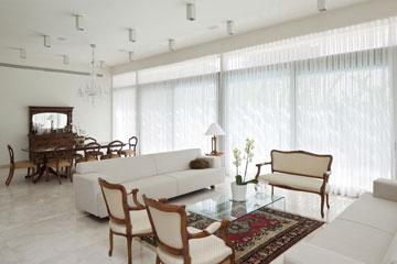 בסלון שני קירות זכוכית שפונים לגינה ולבריכה (צילום: עמית גרון)