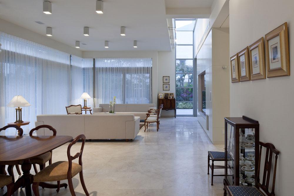 חלל מוארך חוצה את הבית לכל גובהו. בחלקו הצפוני הוא מגדיר את החלוקה בין הסלון למטבח ומכניס אור טבעי שיורד מה''סקיי-לייט'' לקומת הכניסה (צילום: עמית גרון)