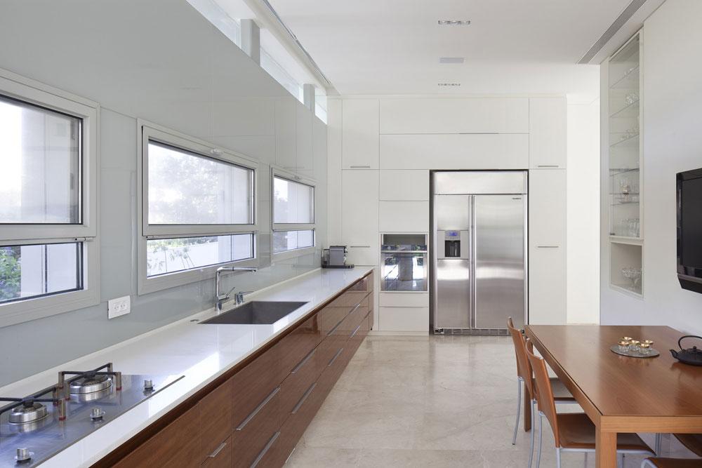 מצידו השני של קיר המדיה מטבח לבן ונקי קווים, עם רצועות חלונות רוחביים שמכניסות אור רב ומשקיפות לרחוב (צילום: עמית גרון)