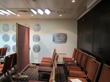 חדר בית הכנסת שעל קירותיו העתקים מוגדלים של מטבעות עתיקים שנמצאו בחפירות ארכיאולוגיות  (צילום: מיכאל יעקובסון)