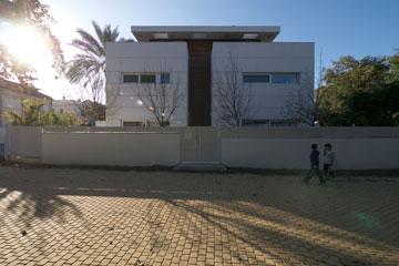 הכניסה. חזית אטומה ככל האפשר, דלת ששולבה בחלון אנכי מחופה סרגלי עץ, וגג ''מרחף'' שמחבר בין שני צדי המבנה (צילום: איתי סיקולסקי)