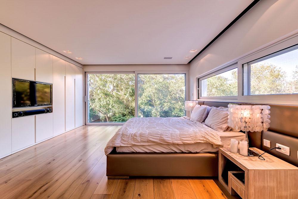 חדר השינה של ההורים, בקומה העליונה. חלון גדול שפונה לבריכה ולגינה הציבורית שמול הבית, מיטה מרופדת בעור, וחדרי רחצה וארונות צמודים (צילום: איתי סיקולסקי)