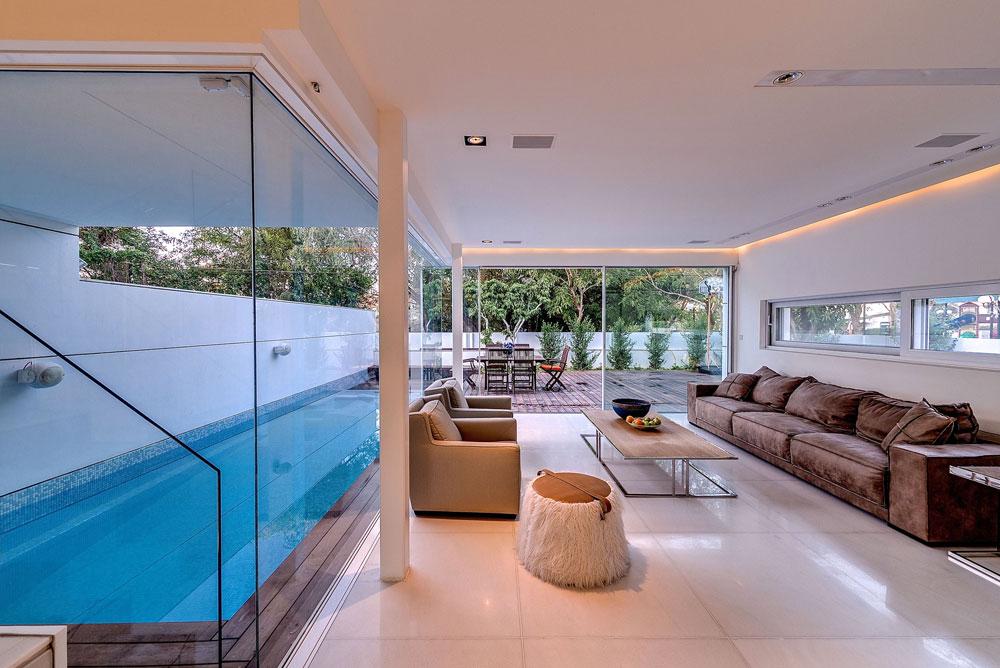 עמודים תומכים מפלדה לבנה איפשרו לבנות בסלון שני קירות מזכוכית. מעל תקרה ''צפה'', שסביבה פסי תאורה נסתרת (צילום: איתי סיקולסקי)