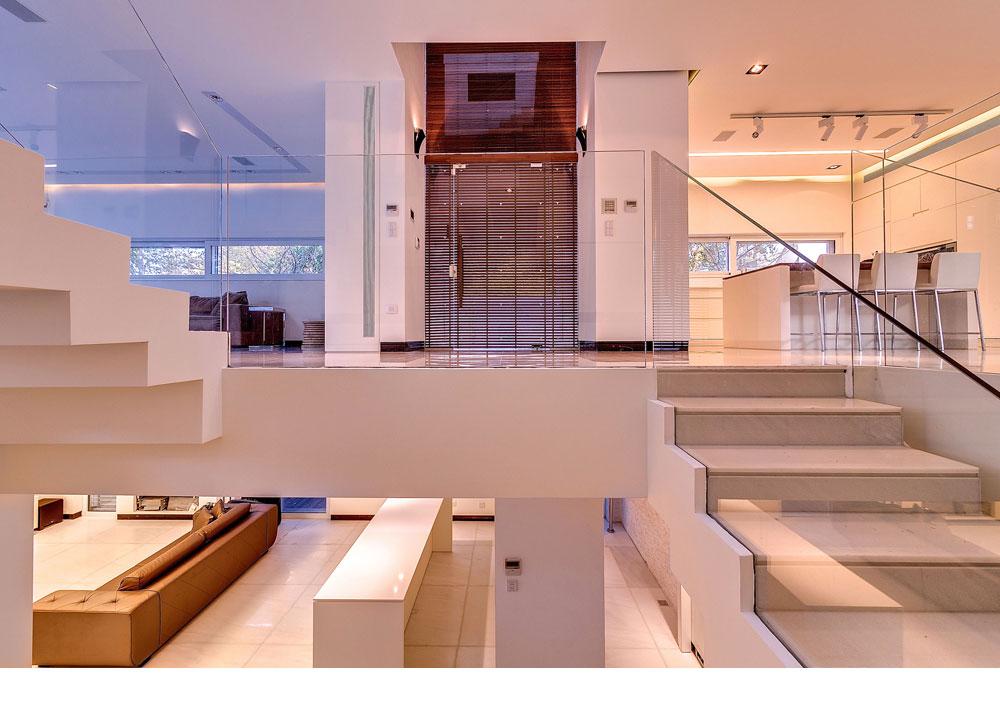 מבט אל דלת הכניסה מגרם המדרגות היורד לקומת המרתף, שבה חדר קולנוע ומשרד. המרתף מואר בזכות חצרות אנגליות (צילום: איתי סיקולסקי)