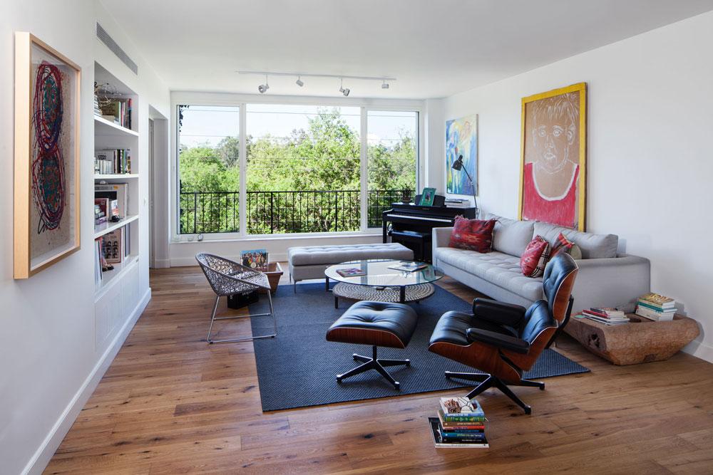 הסלון מוקם מול נוף הפארק, שאליו פונה הדירה. החלונות הוחלפו, הרהיטים בסגנון מודרני קלאסי, וצבע מוסיפים לחלל ציורים שצייר הדייר (צילום: טל ניסים)