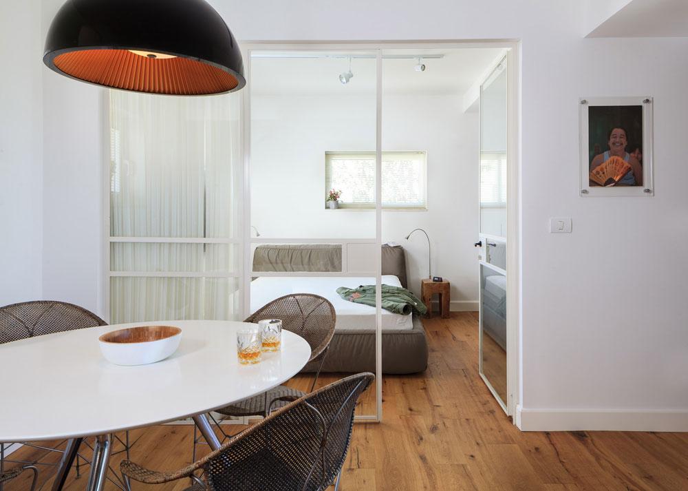 וילון סאטן לבן מספק פרטיות כשצריך. שולחן האוכל הובא מדירתו הקודמת של הדייר.  כסאות הראטן, המנורה שחורה והמיטה האפורה ברקע משלימים את פלטת הצבעים הבסיסית של הדירה (צילום: טל ניסים)