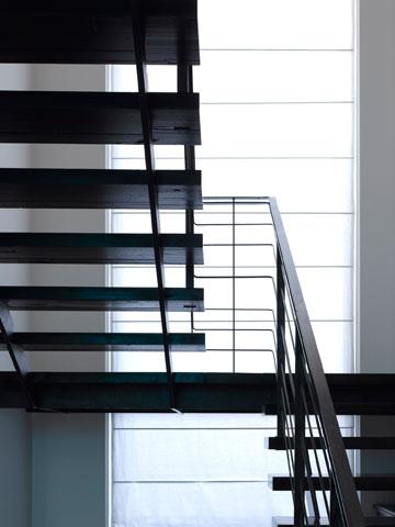 מדרגות עץ שחורות ומעקה ברזל (צילום: עמית גרון )