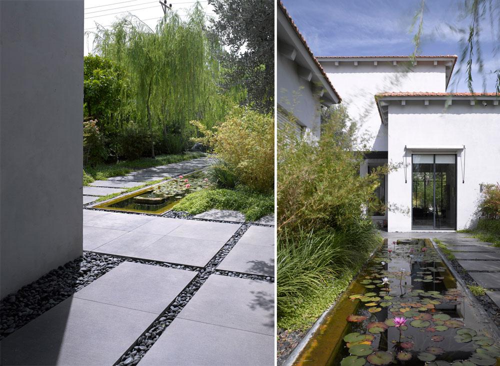 מדרכי אבן שחורה מובילים לדלת הכניסה הרחבה של הבית. הגן מטופח ומתוכנן לפרטי פרטים, כול בריכת חבצלות (צילום: עמית גרון )