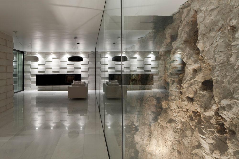 בבית פרטי בירושלים האבן המקומית היא החומר הדומיננטי בעיצוב: מסלעה טבעית שהיתה במגרש נתחמה בזכוכית והפכה ללב הבית (צילום: עמית גרון )