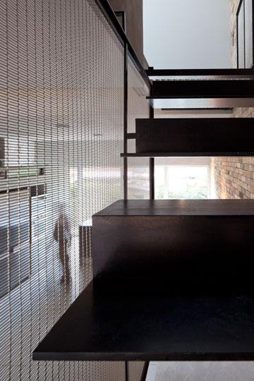 מעקה רשת, מדרגות ברזל וקיר לבנים חומות (צילום: עמית גרון )