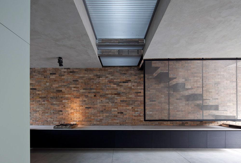 האור חודר למעלה לקומת חדרי השינה, ומגיע לקומת הכניסה דרך רצפת המסדרון, שעשויה רשת דקה. אותה רשת היא גם מעקה מדרגות הברזל (צילום: עמית גרון )