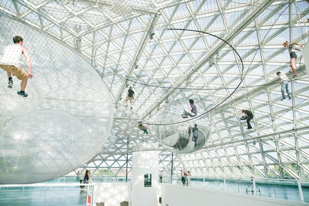 בדיסלדורף, גרמניה, מרחפים וצפים בבועות התלויות בין רשתות ענקיות במיצג של תומאס סראסנו (צילום: Cc, studio tomas saraceno)