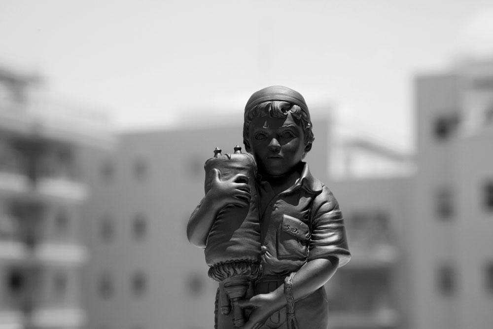בובת ויניל של שין למד, על רקע אורבני. הוא יוצר רק בשחור-לבן: ''זה יותר זול ואני מאמין שזה גם מבטא יפה את הקוטביות של החיים שלי'' (צילום: ג'יל שוובר)