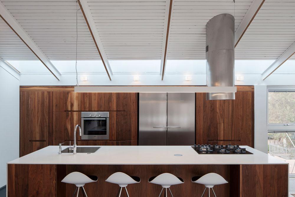 סקיי-לייט מאיר גם את המטבח, שעוצב בלבן ובעץ אגוז. בגלל שהעירייה מתירה מרפסת רק בקומה העליונה, ובזכות גובה החלל, מוקמו הסלון והמטבח למעלה, וחדרי השינה דווקא בקומת הכניסה, למטה (צילום: אביעד בר נס)