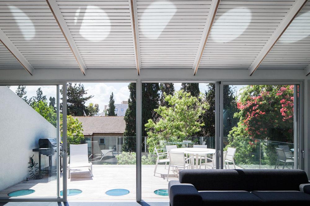 החלונות העגולים שברצפת המרפסת, למשל, מאירים את פינת המשפחה בקומה שלמטה (צילום: אביעד בר נס)