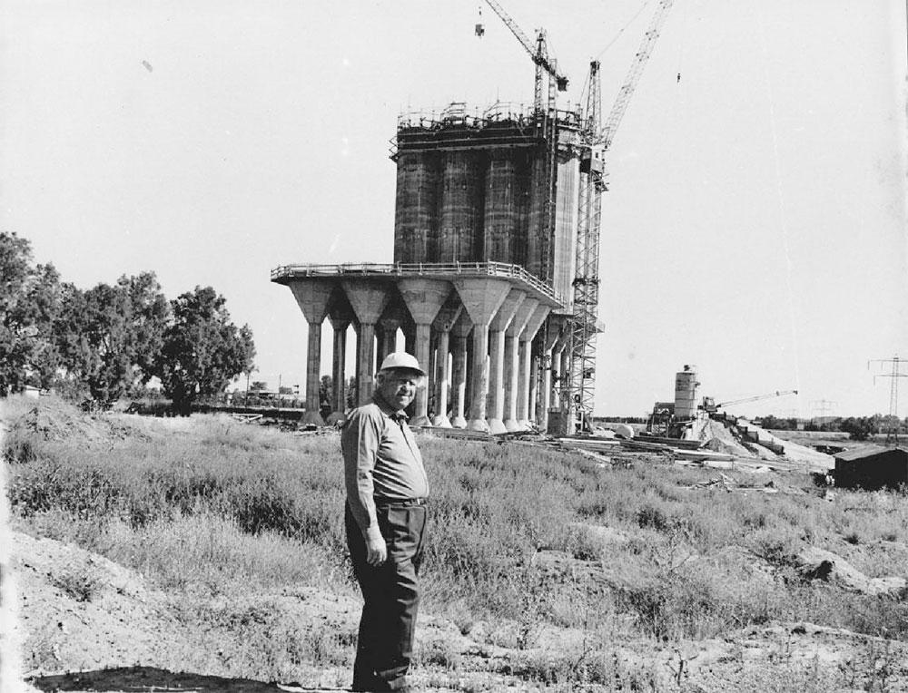 המהנדס יוסף אידלמן על רקע ממגורה בקריית גת שתיכנן בסוף שנות ה-60. בתערוכה יוצגו צילומי האסמים במצבם הנוכחי לצד מסמכים אדריכליים וצילומים של הקמתם (באדיבות ארכיון אדריכלות ישראל )